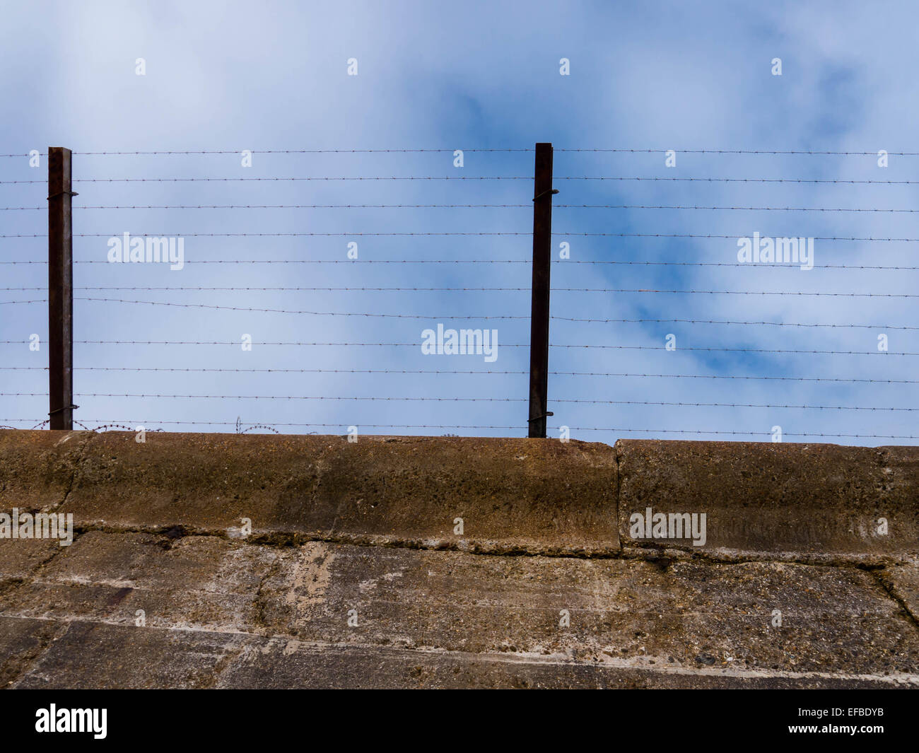 A barbed wire fence on top of a concrete wall - Stock Image