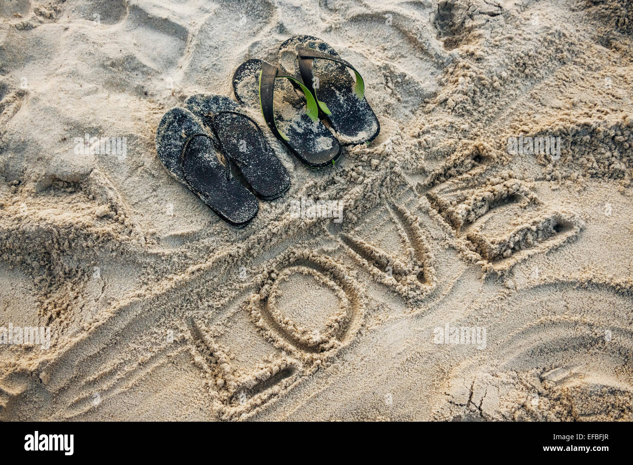 Sand writing of the word LOVE with a couple sandals - Stock Image