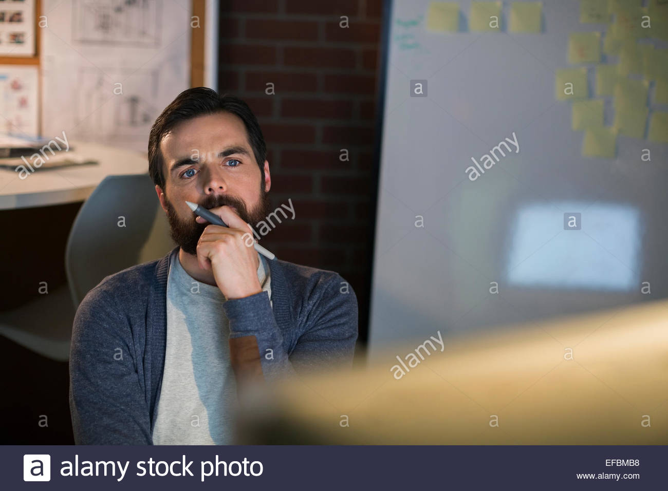 Serious designer working late at computer in office - Stock Image