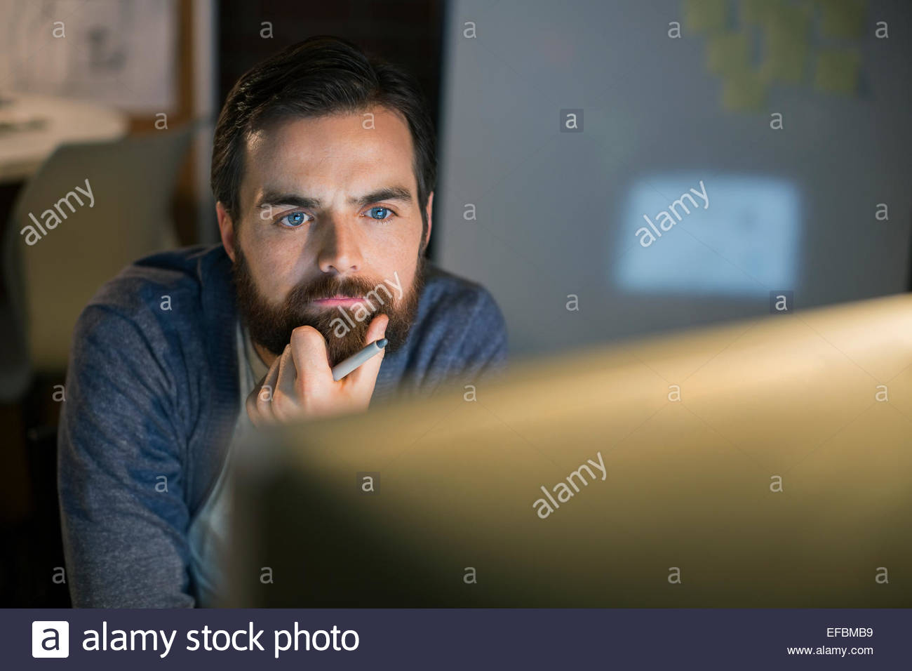 Serious businessman working late at computer in office - Stock Image