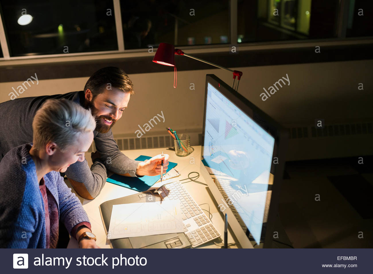 Business people working late at computer in office - Stock Image