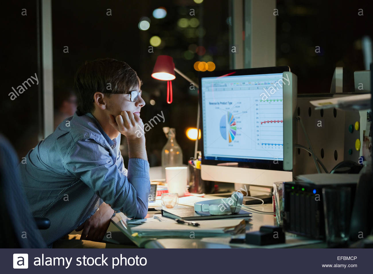 Businessman working at late at computer in office - Stock Image