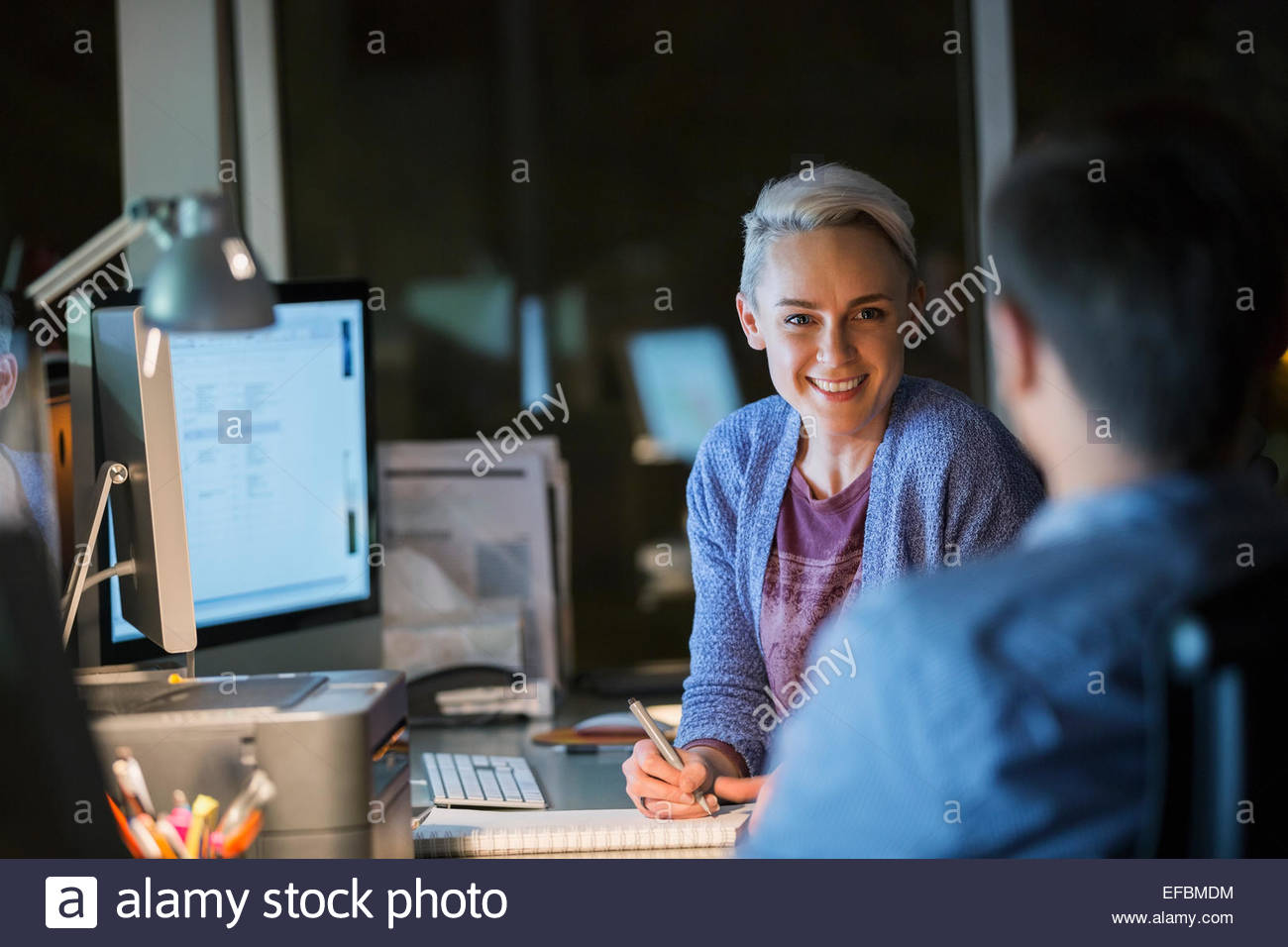Business people working late in office - Stock Image