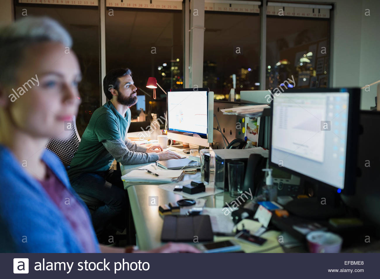 Business people working late at computers in office - Stock Image