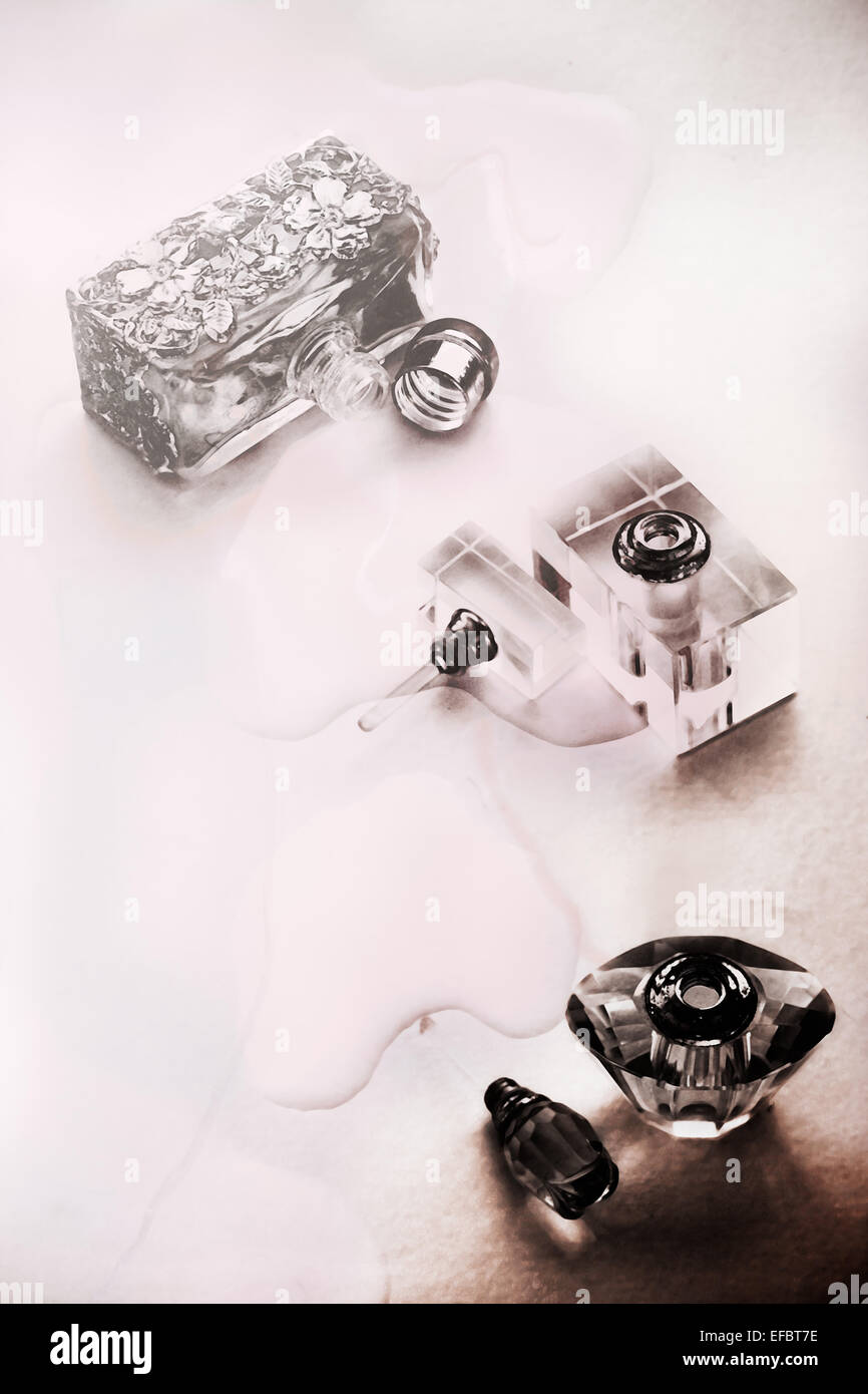 Three fancy perfume bottles, lids off and spilt perfume on table - Stock Image