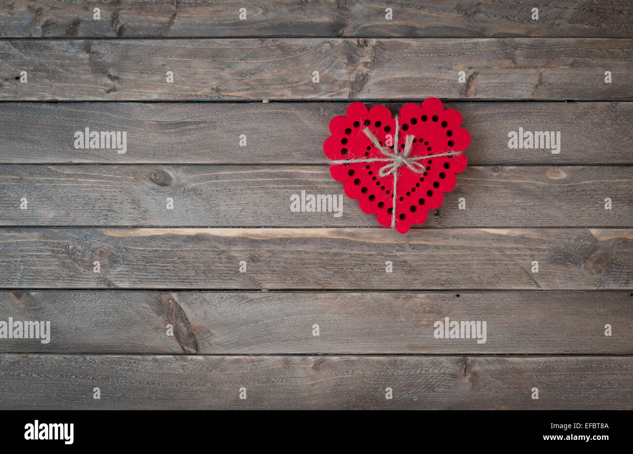 Heart shapes tied together on a wooden background. - Stock Image
