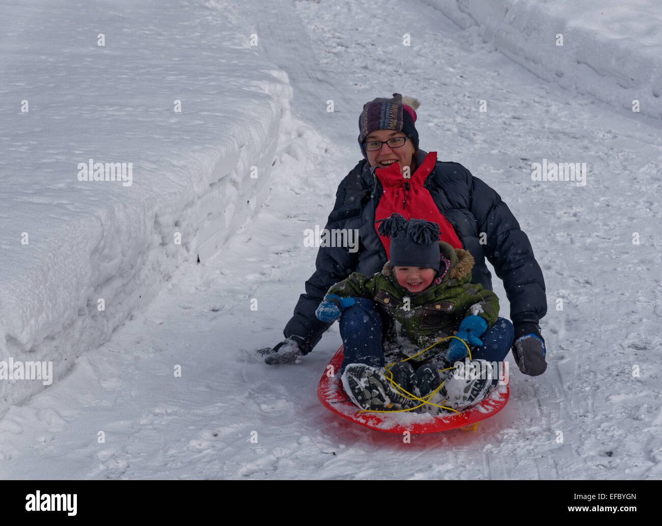 Mother and son sledging together - Stock Image
