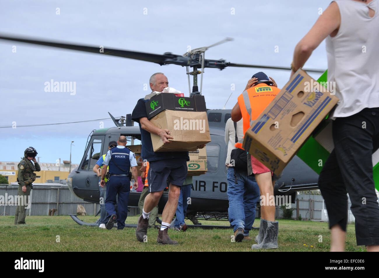 CHRISTCHURCH, NEW ZEALAND, February 22, 2011: Volunteer relief workers scramble for food supplies from an Air Force - Stock Image