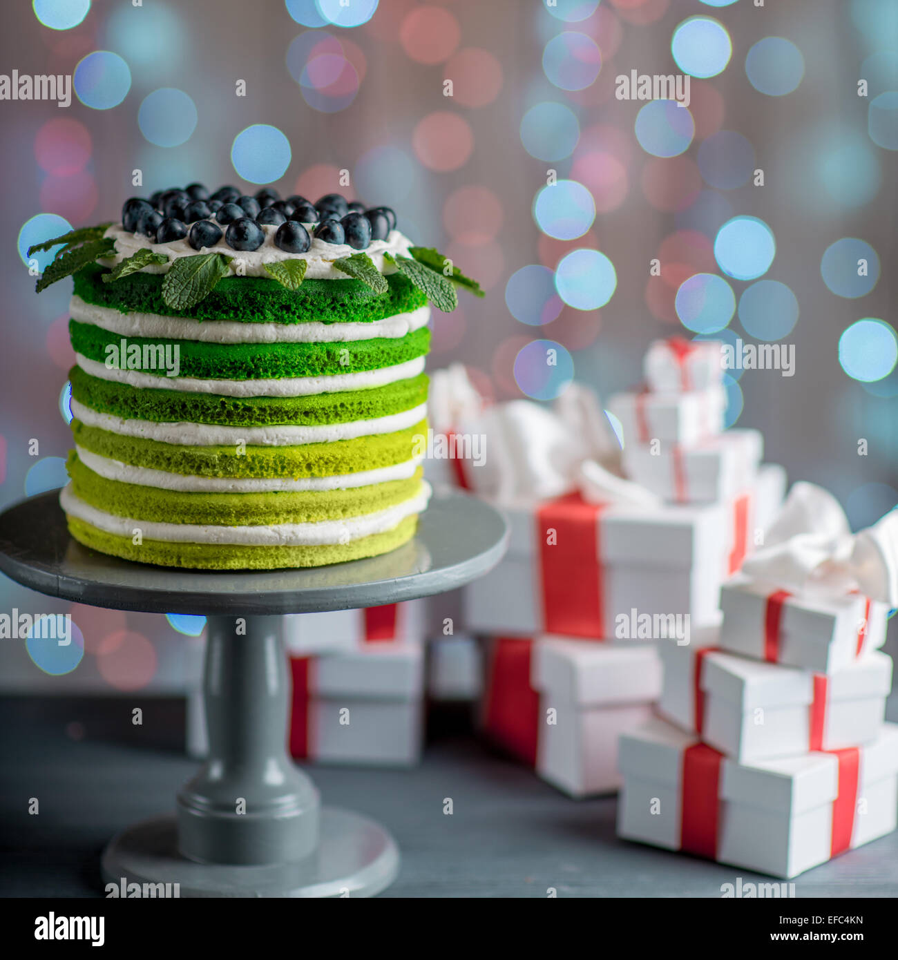 Nice Sponge Happy Birthday Cake With Mascarpone And Grapes On The Stand Gift Boxes Festive Light Bokeh Backgro