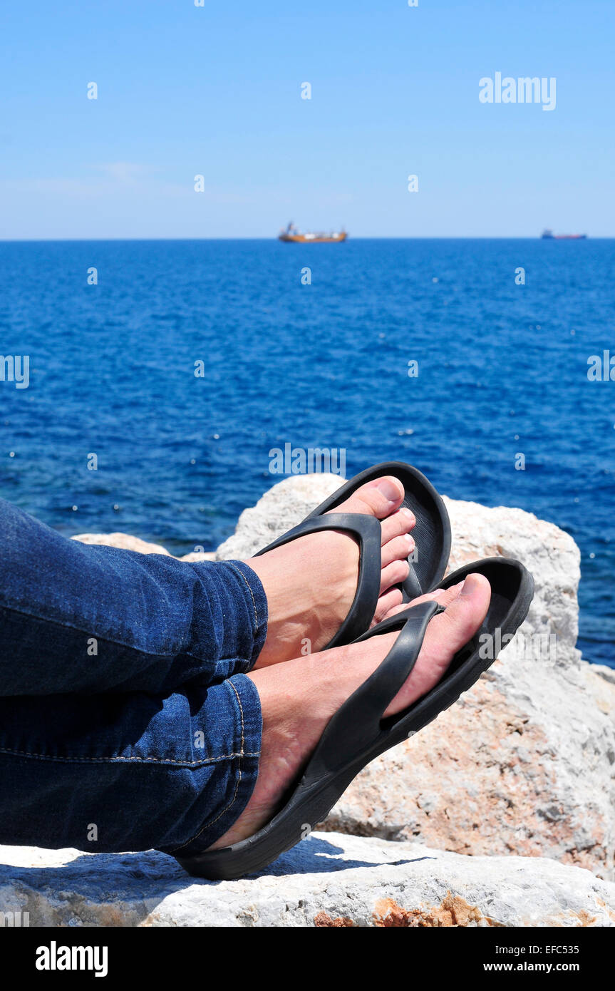 7c3d8cd8f41b closeup of the feet of a man with flip-flops who is relaxing near the