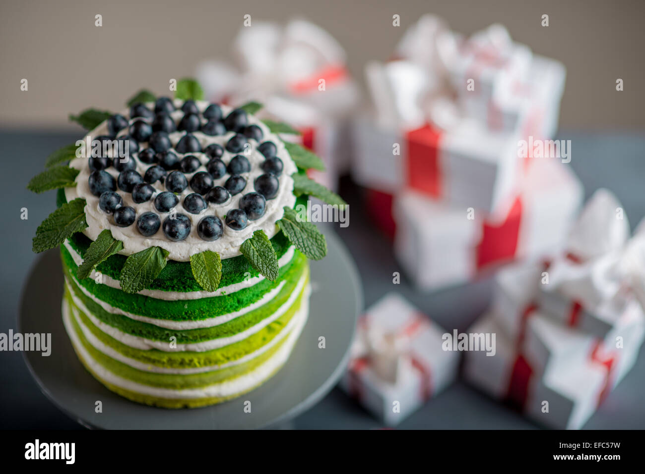 Nice sponge happy birthday cake with mascarpone and grapes with on the cake stand with gift boxes on festive light - Stock Image