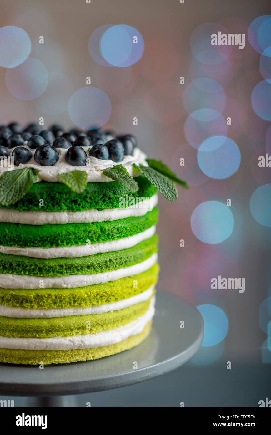 Nice sponge happy birthday cake with mascarpone and grapes on the cake stand on festive light bokeh - Stock Image