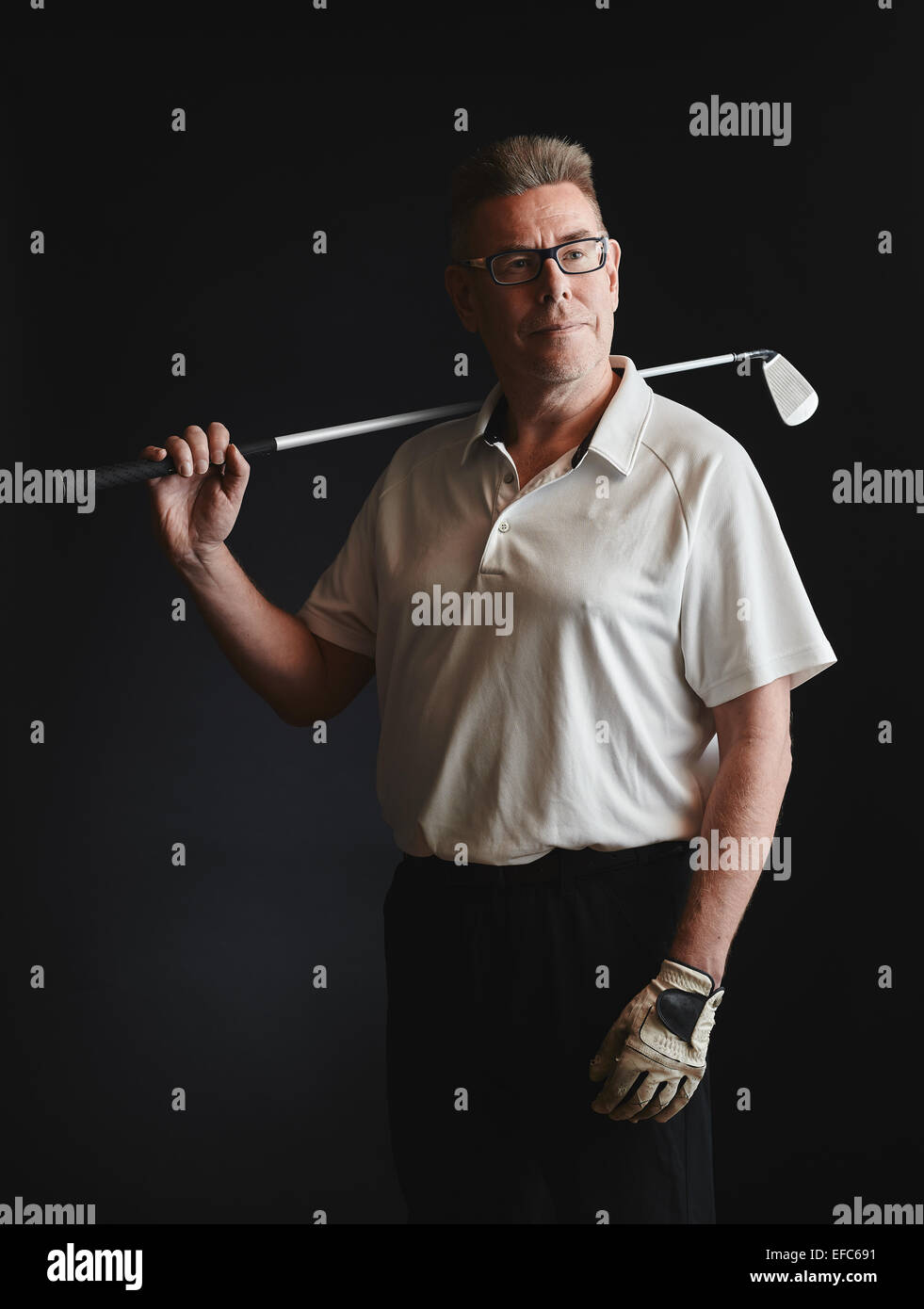 Mature man golfer wearing a white shirt and hold a iron golf club on his shoulder - studio shot, black background - Stock Image