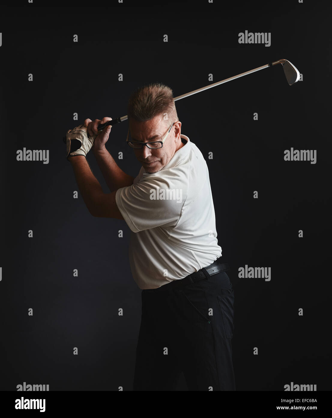 Mature man golfer wearing a white shirt and he exercise a swing - studio shot, black background - Stock Image