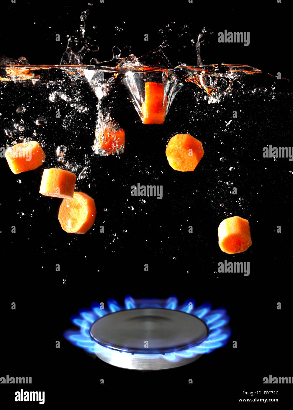 A conceptual image of a gas hob with sliced carrots being dropped into boiling water - Stock Image