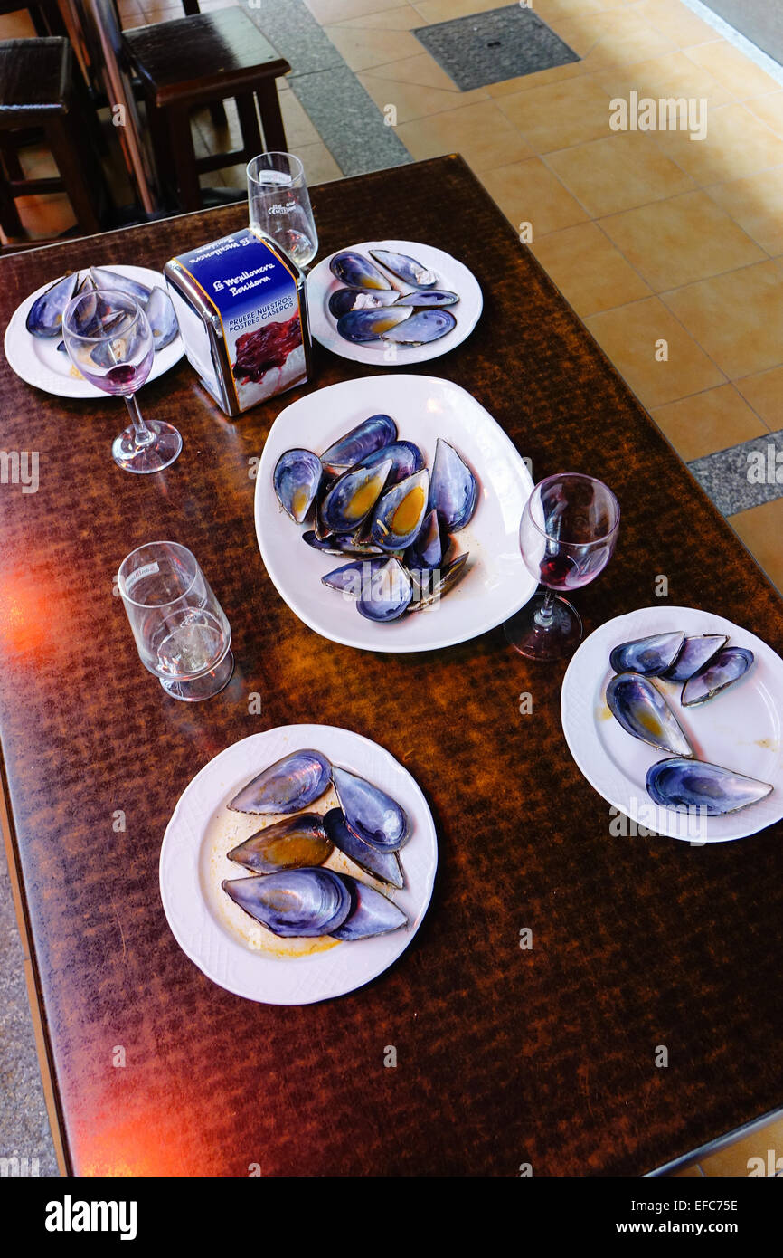 Empty mussel shells on  five white plates with empty wine glasses on a table, Benidorm, Costa Blanca, Spain after - Stock Image