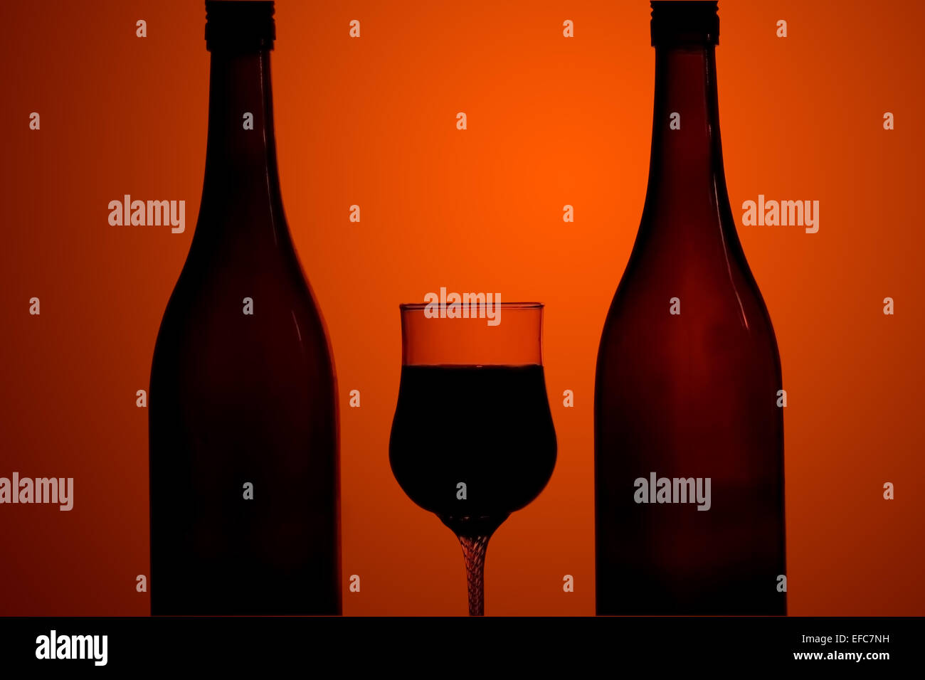 Atmospheric image of two bottles of wine and a wine glass silhouetted against a graduated orange background - Stock Image