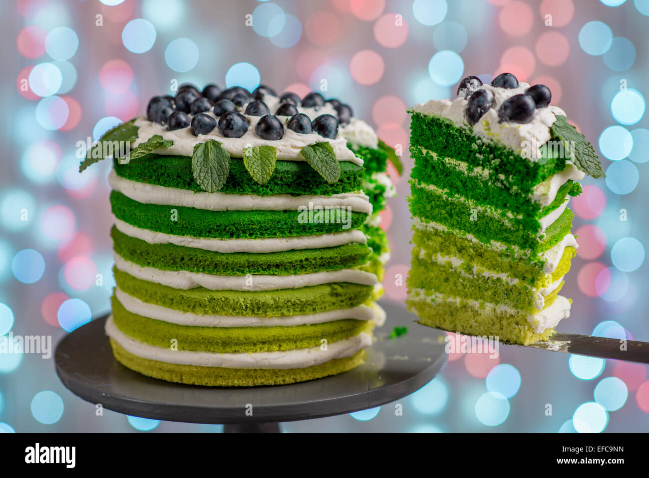 Cutting beautiful green sponge cake on festive background with bokeh light - Stock Image