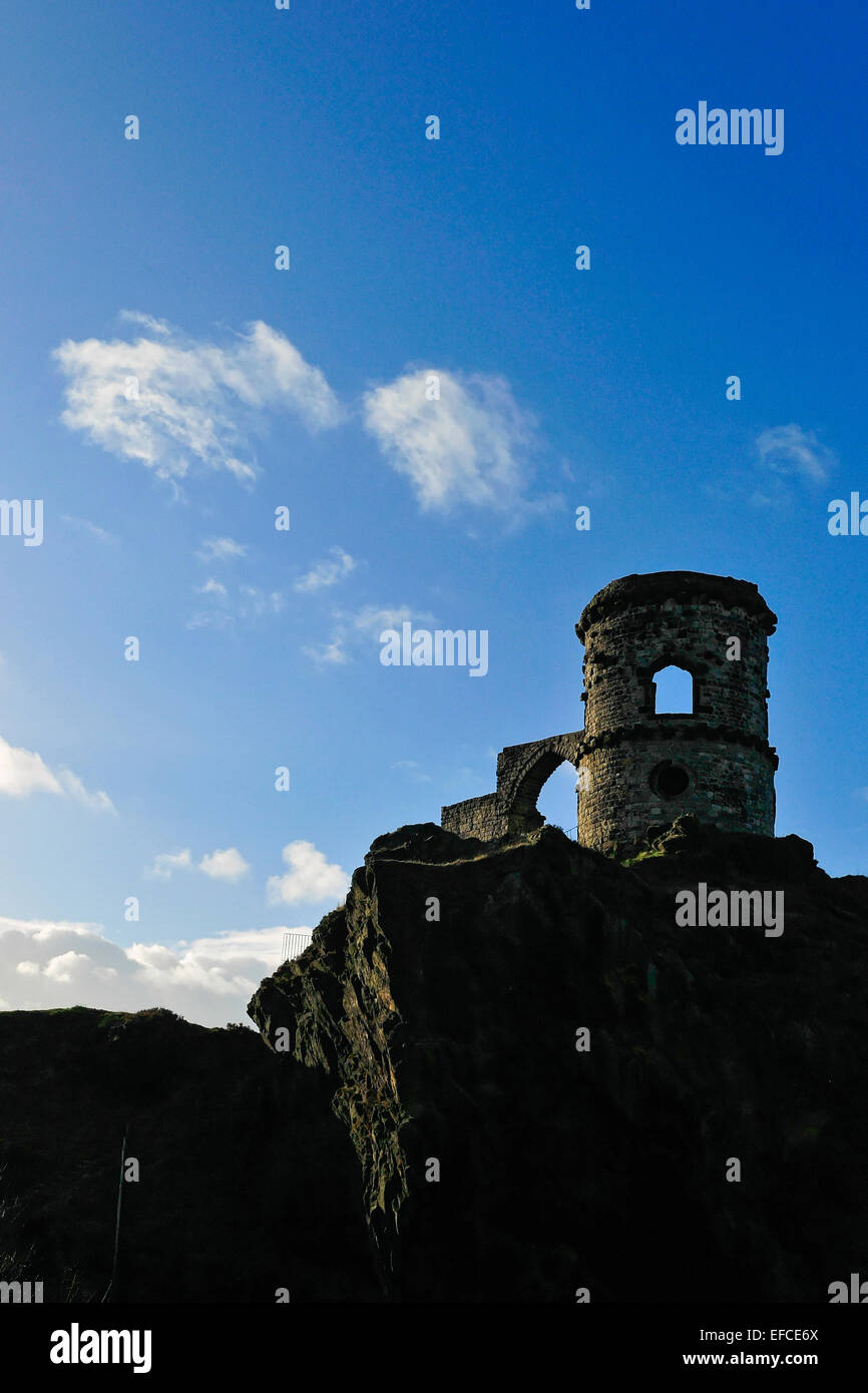 Mow Cop Castle, a folly on the Cheshire-Staffordshire border; silhouetted against blue sky with white clouds. - Stock Image