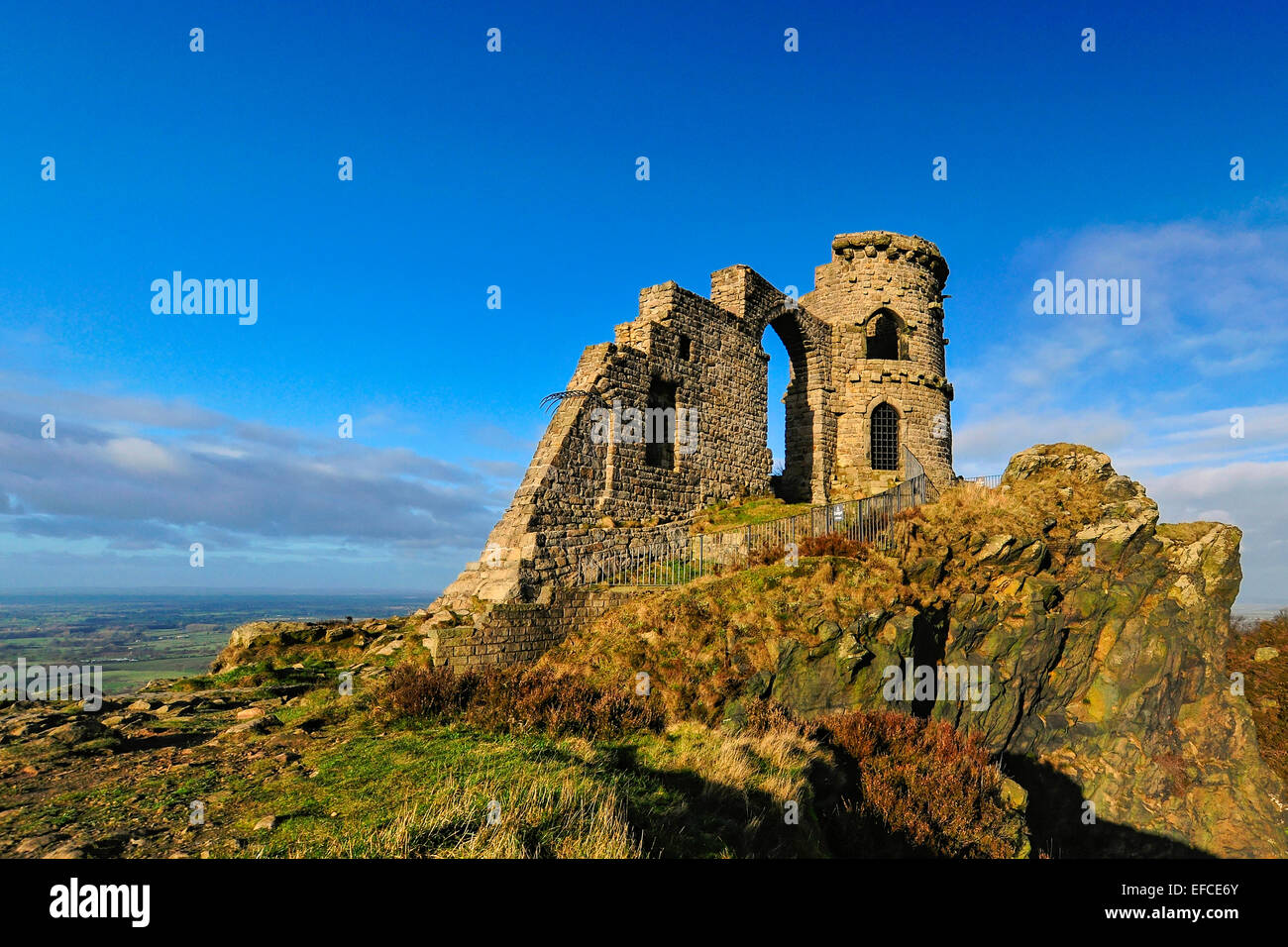 Mow Cop Castle, a folly on the Cheshire-Staffordshire border; landscape in background; blue sky with white clouds. - Stock Image
