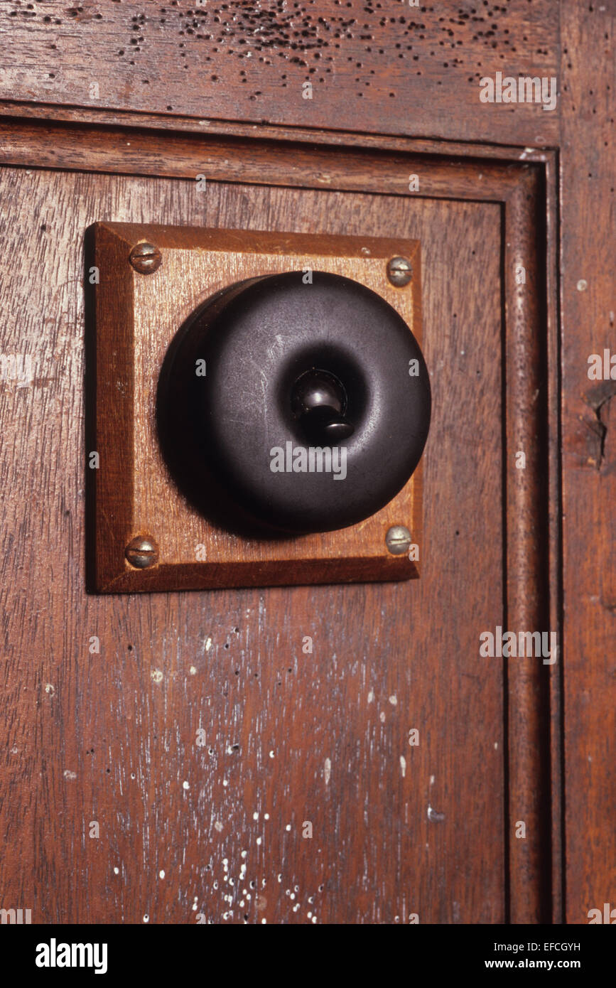 Vintage bakelite black electric light switch mounted on wood and screwed to wooden panel with signs of wear Stock Photo