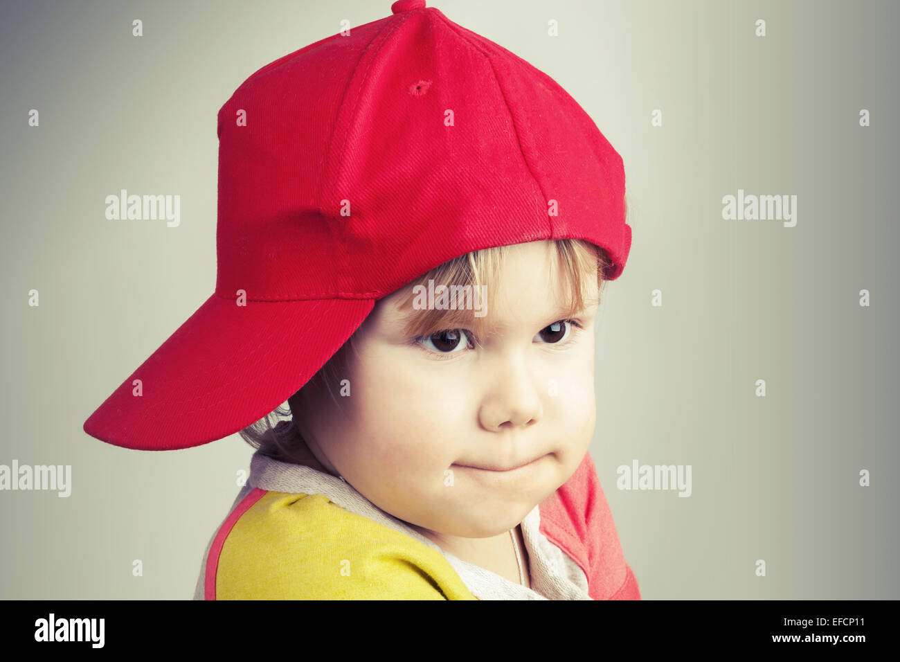 631995bc4 Studio portrait of funny baby girl in red baseball cap over gray ...