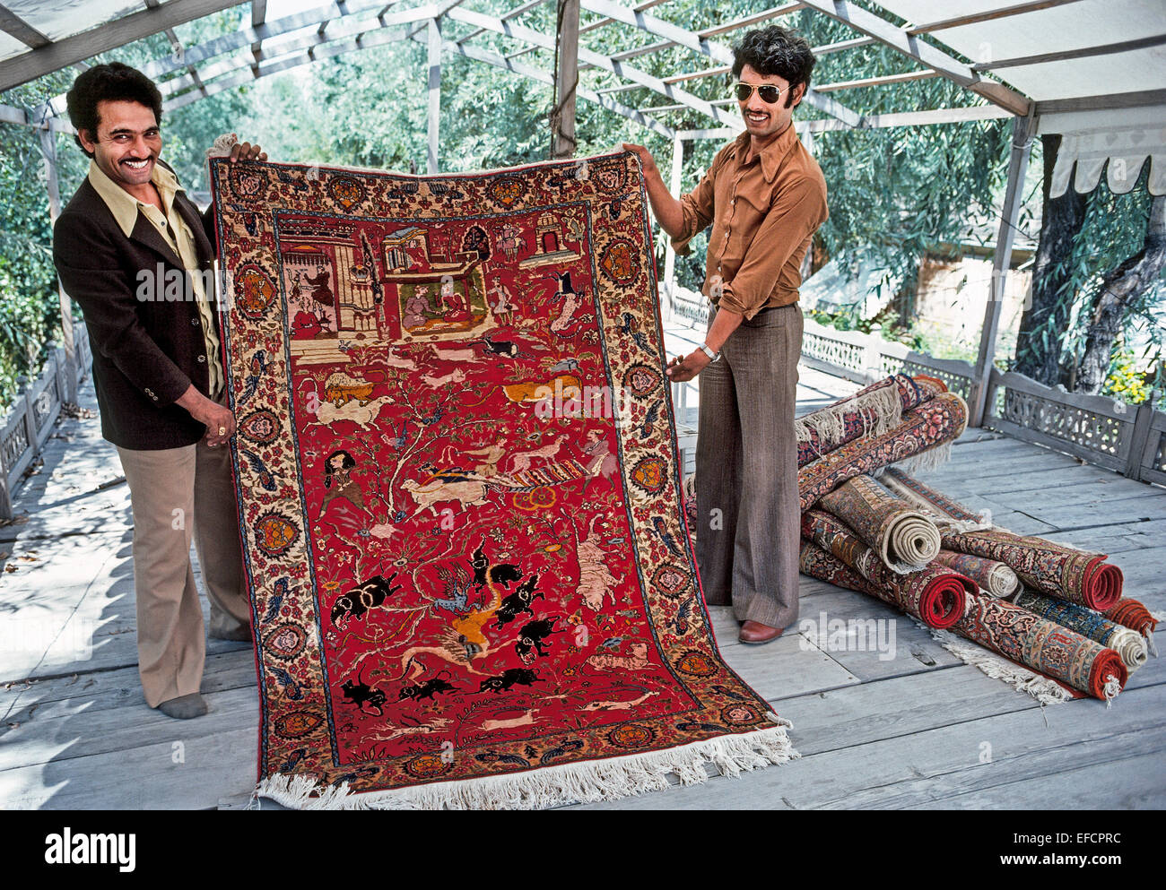 Two Kashmiri salesmen proudly display traditional hand-woven Oriental rugs to visitors at Dal Lake in Srinagar in - Stock Image