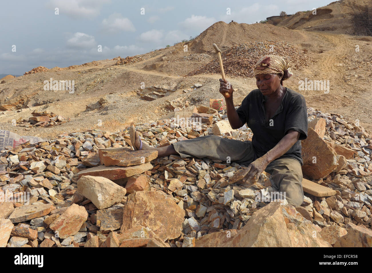 A woman works breaking rocks into gravel at a quarry near Accra, Ghana, West Africa. - Stock Image