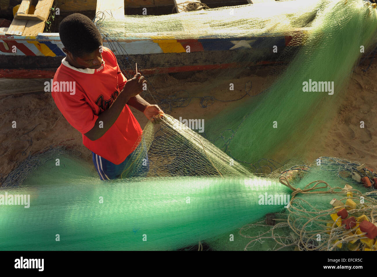 A fisherman mends his nets along the Gold Coast near Accra, Ghana, West Africa. - Stock Image