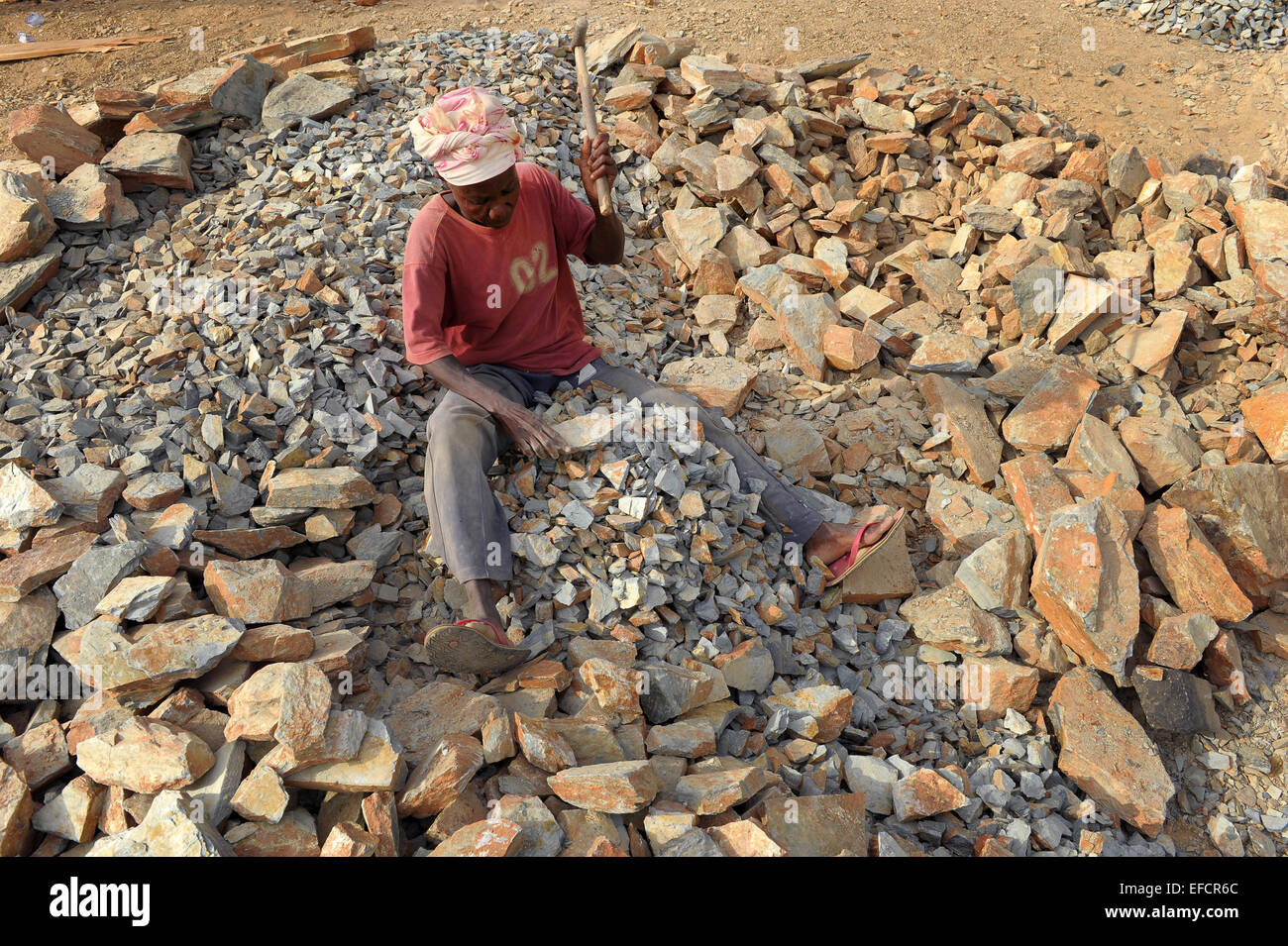 A woman at work breaking rocks into gravel in a quarry near Accra, Ghana, West Africa. - Stock Image
