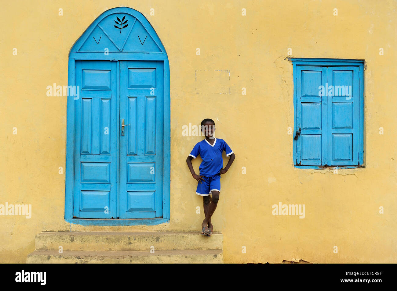 A boy in blue in front of a church in Esiam, Ghana, West Africa. - Stock Image