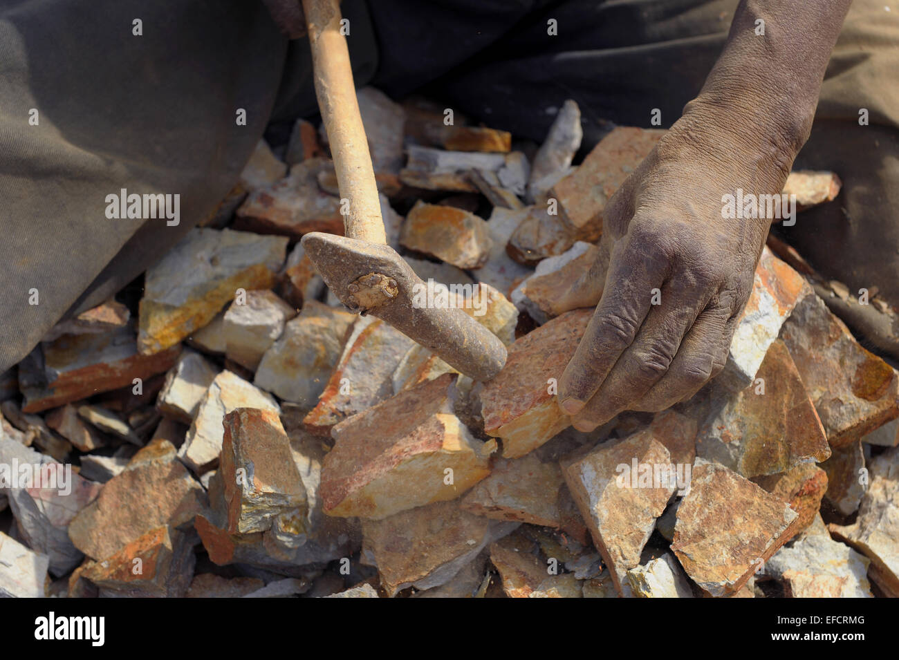 Breaking rocks by hand in a quarry near Accra, Ghana, West Africa. - Stock Image