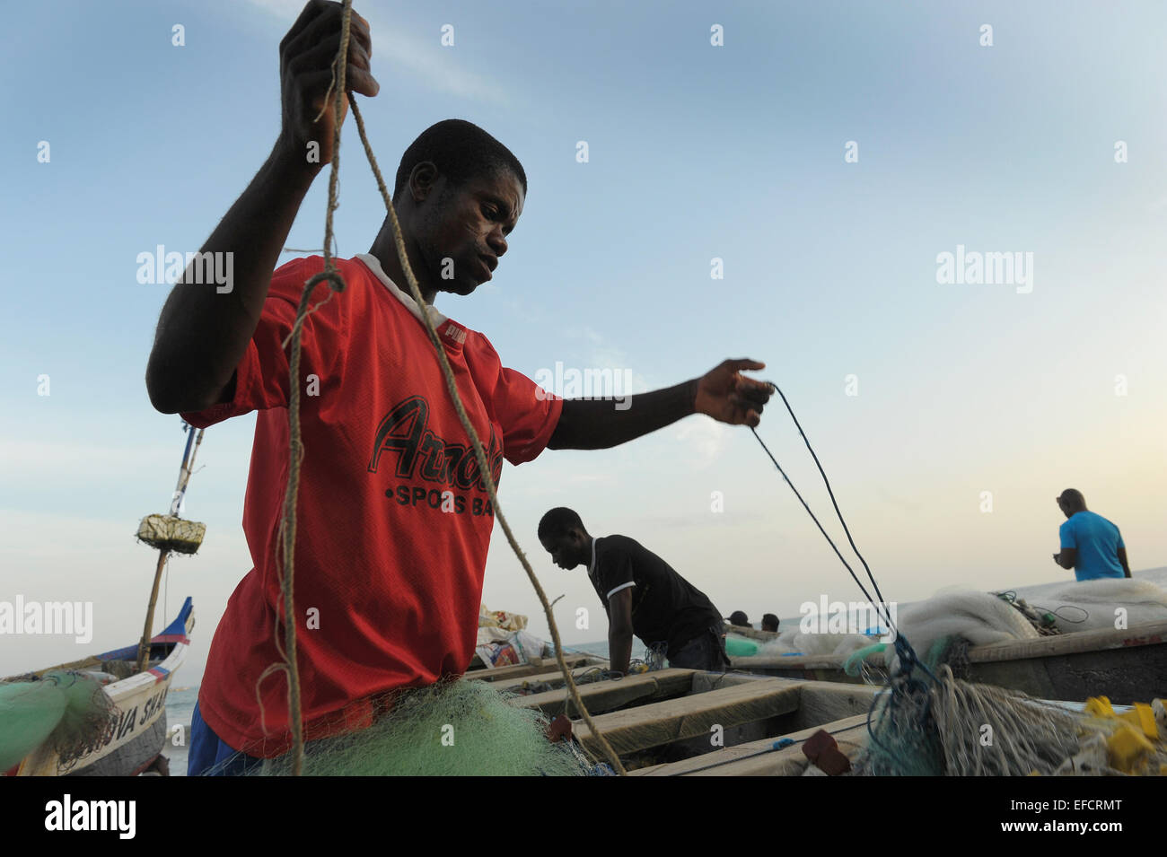 Fishermen stowing their nets after a day of fishing of the coast of Accra, Ghana, West Africa. - Stock Image
