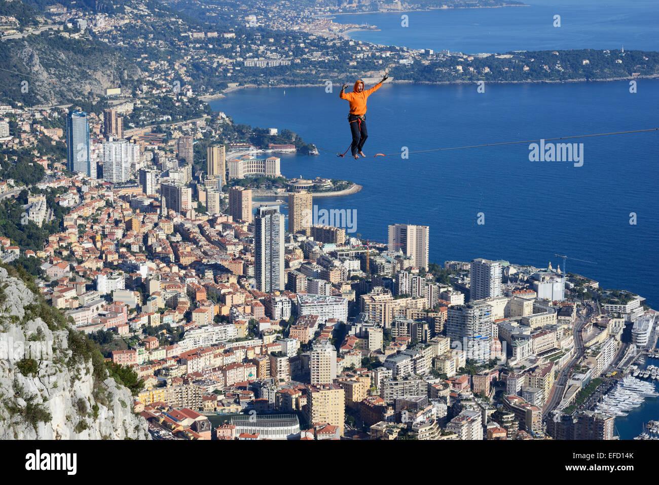 YOUNG MAN HIGHLINING (SLACKLINING) at an elevation of 550m amsl. Principality of Monaco below him. - Stock Image
