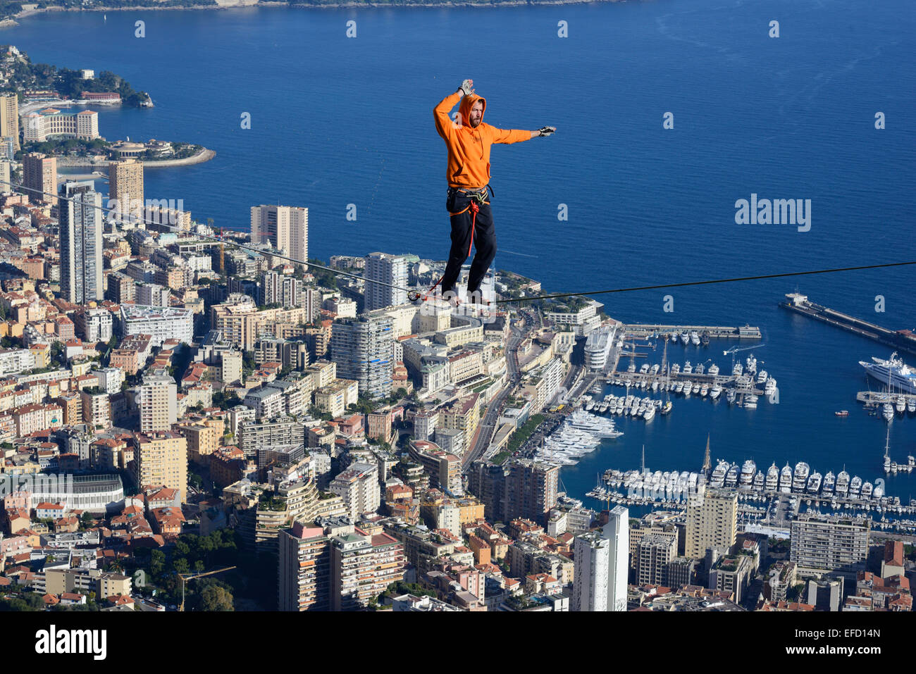 YOUNG MAN HIGHLINING (SLACKLINING) at an elevation of 550m amsl. Monte-Carlo District in the Principality of Monaco - Stock Image