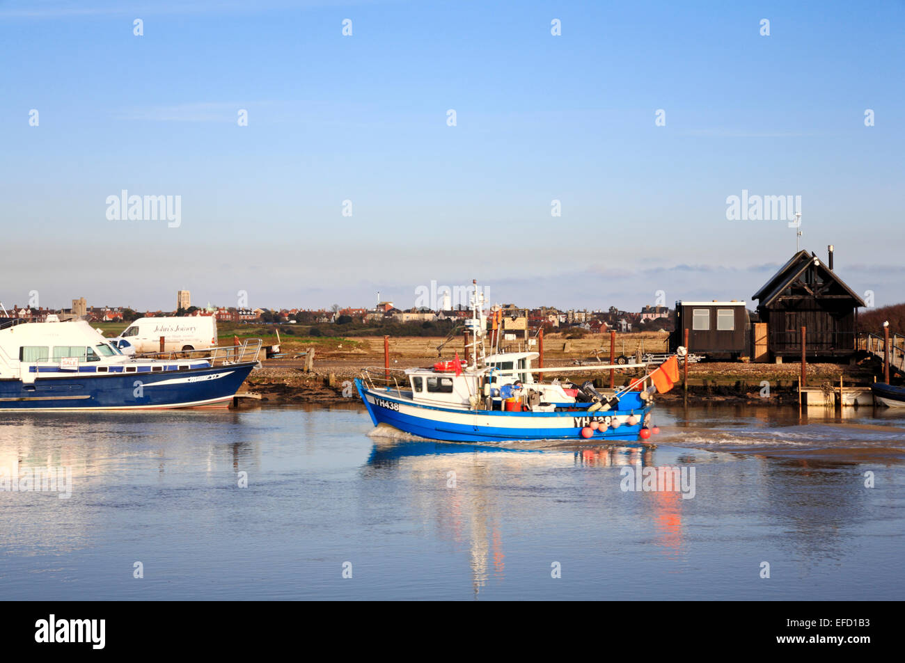 An inshore fishing boat returning up the River Blyth to the harbour at Southwold, Suffolk, England, United Kingdom. - Stock Image