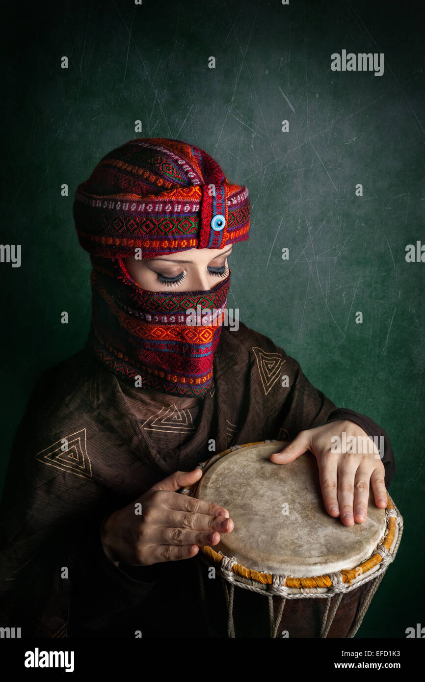 Oriental woman in turban playing drum at green textured wall - Stock Image