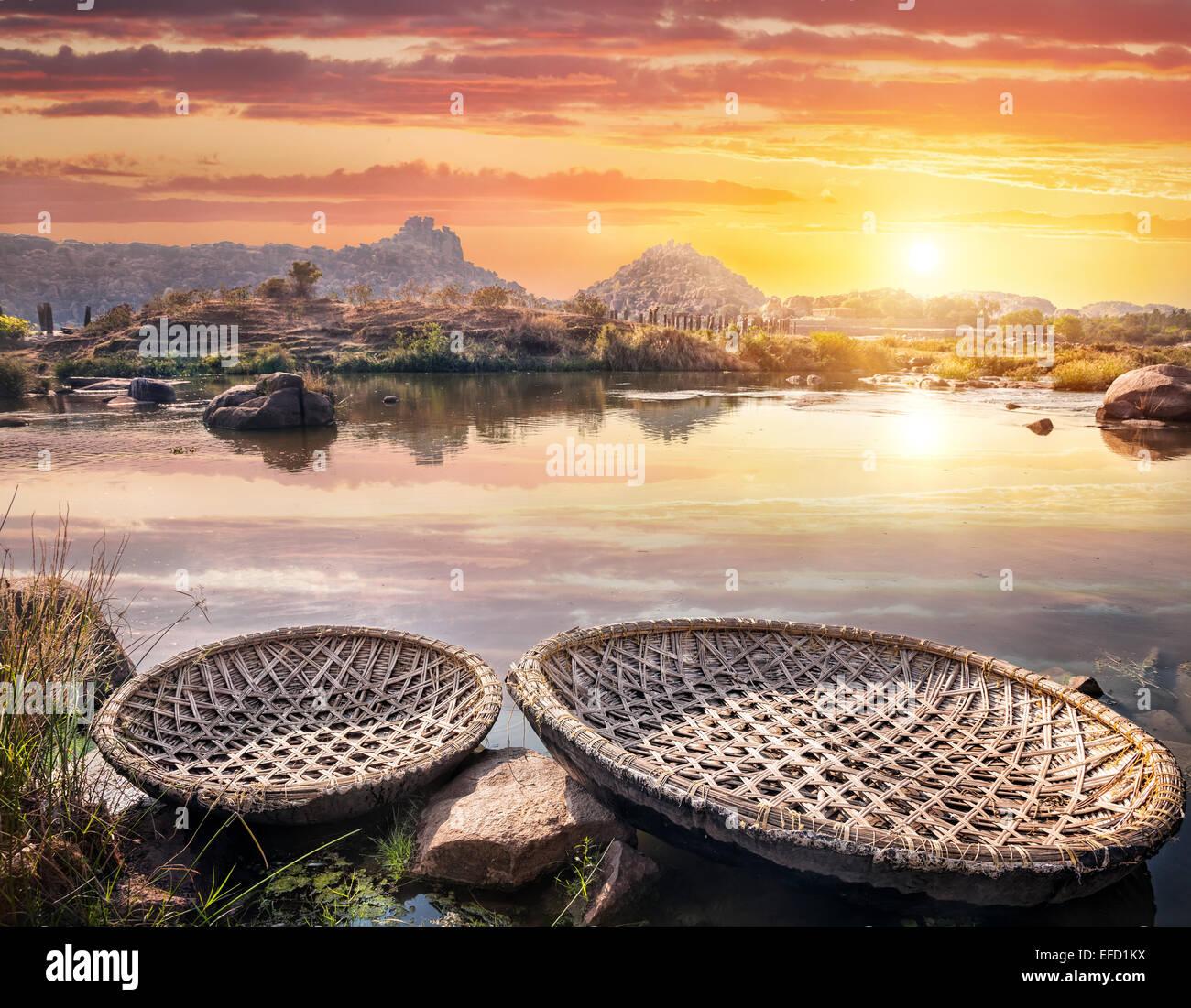 Round shape boats on Tungabhadra river at sunset sky in Hampi, Karnataka, India - Stock Image