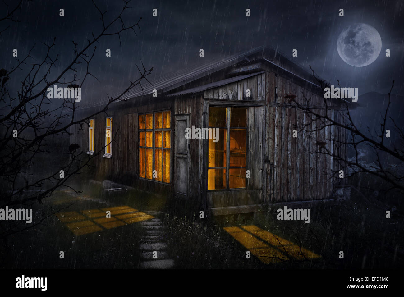 Rural house with glowing windows at night sky with moon - Stock Image