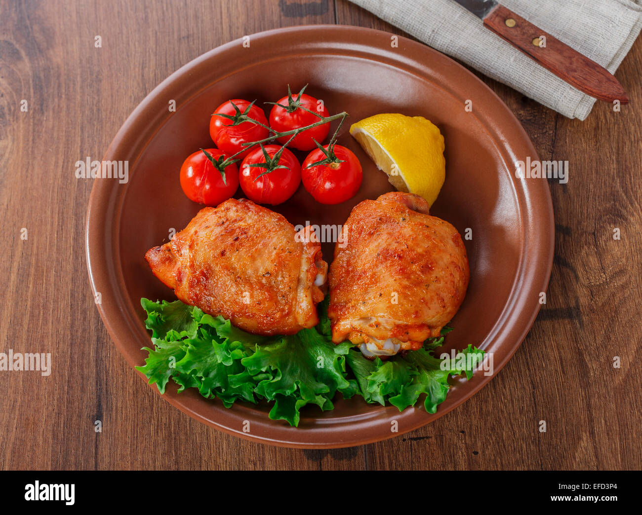 baked chicken thigh with cherry tomatoes and lemon - Stock Image