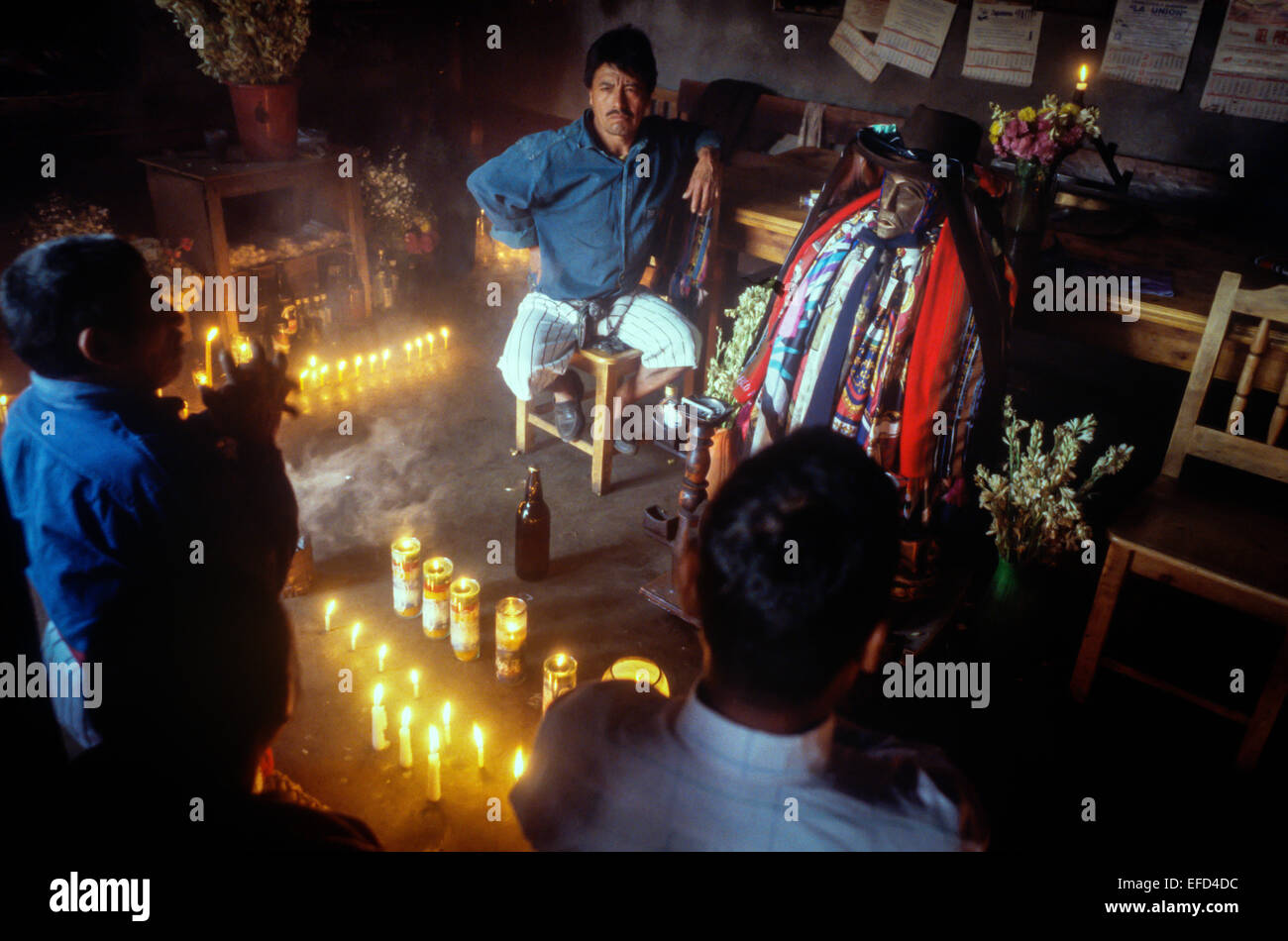 Several men pray and make offerings to Maximon - Stock Image