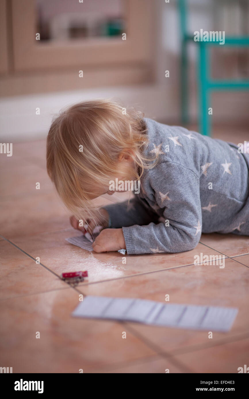 Toddler lying on floor and drawing on paper. - Stock Image