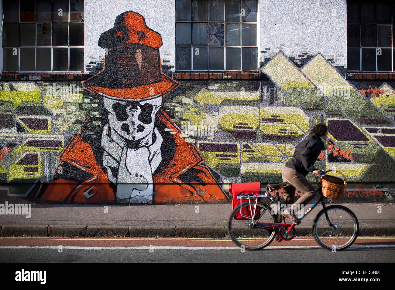 A woman cycles past a piece of urban street art and graffiti on the side of a building in Stokes Croft, Bristol. - Stock Image