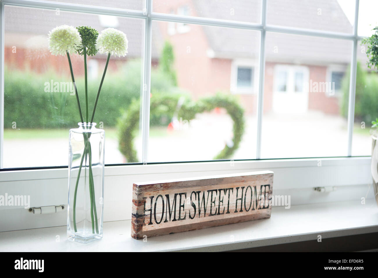 on a window sill in the house is a sign with the text home sweet home - Stock Image