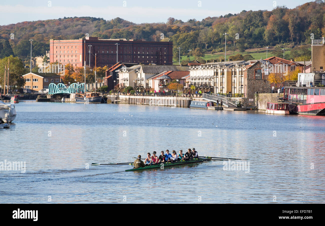 A crew of rowers make their way through the water of the floating dock in Bristol on a sunny day. - Stock Image