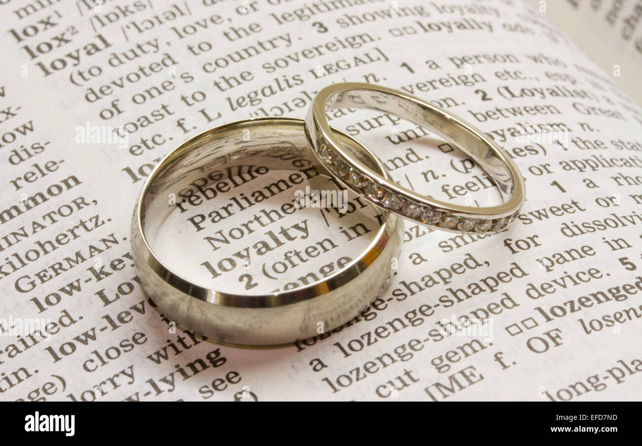 Wedding rings depicting word loyalty - Stock Image