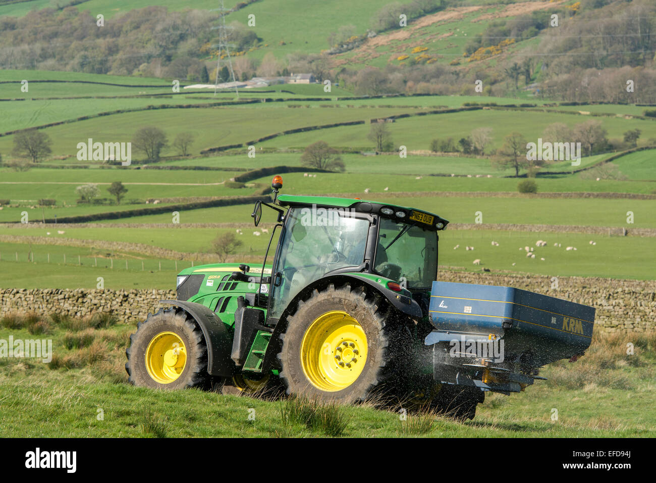 John Deere 6126r spreading fertiliser on upland pasture, Lancashire, UK. - Stock Image