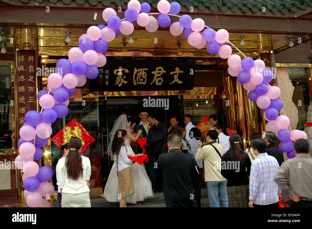 Chengdu, China:  A wedding party standing in the entry door of a restaurant passes out cigarettes and candies to - Stock Image