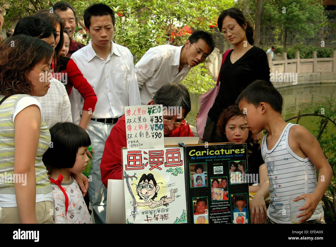 Chengdu, China:  A crowd gathers to watch an artist doing caricatures in the Jin Li Street park - Stock Image