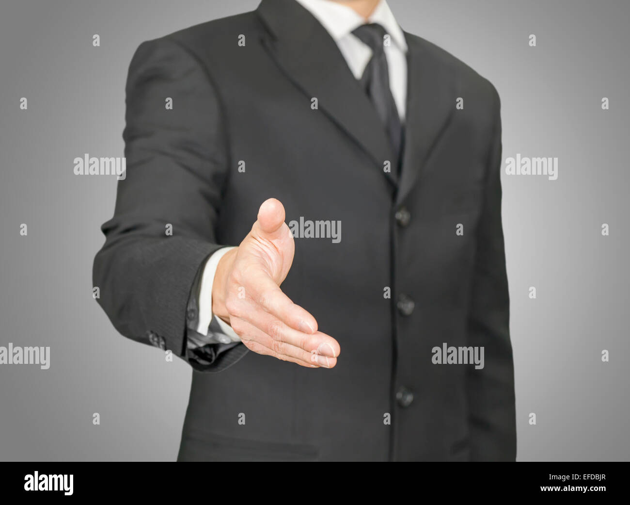 Businessman giving a handshake - Stock Image